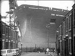 A huge ship bloacks the end of a narrow street, giving the gifted just one way to go.