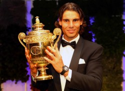 Rafael Nadal in a tuxedo holds up his Wimbledon Championship cup