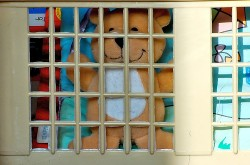 A teddy bear is smiling even though it is trapped behind bars