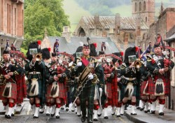 A marching band of scottish soldiers in kilts