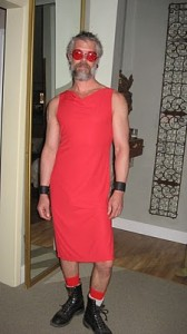 A picture of a bearded man wearing a red dress.