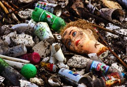 A doll's head lies among toys and beer cans on a garbage heap.