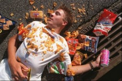 A healthy man is buried under a pile of fast food wrappers